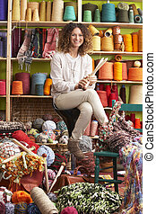 Woman Sitting On Stool Holding Knitting Needles In Front Of Yarn Display