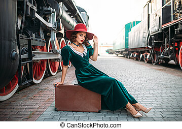 Woman sitting on suitcase against steam train - Young...