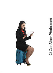 Woman sitting on suitcase looking at computer tablet
