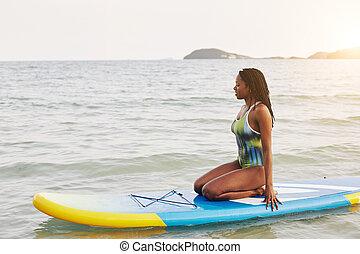 Woman sitting on sup board