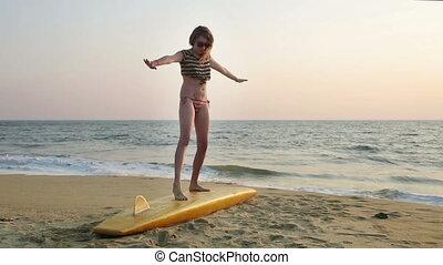 Woman sitting on surfboard - Woman balancing on surfboard