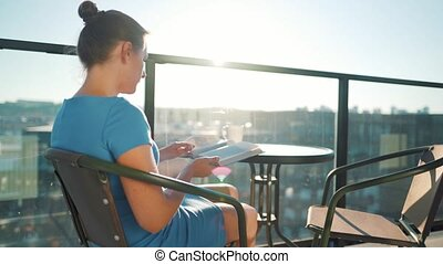 Woman sitting on the balcony and reading a book at sunset - ...