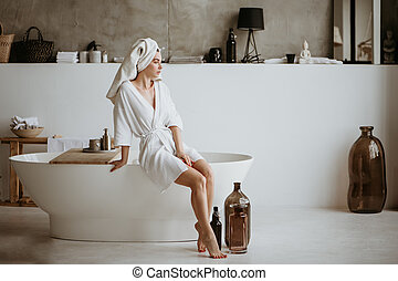 Woman sitting on the bathtub.