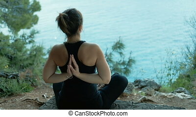 Woman sitting on the beach and holding hands in namaste pose behind.