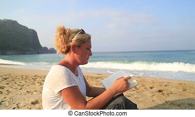 Woman sitting on the beach and read