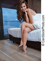 Woman sitting on the bed in night cloth