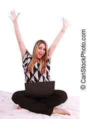 Woman sitting on the bed with a laptop computer and arms up - isolated