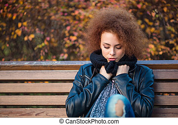 Woman sitting on the bench in autumn park