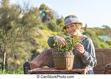 Woman sitting  on the bench with  plant in nature