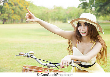 Woman sitting on the bike and pointing forward.