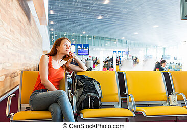 Woman sitting on the chair in a station hall.
