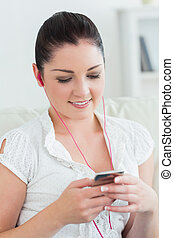 Woman sitting on the couch and listening to music