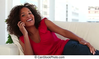 Woman sitting on the couch while calling