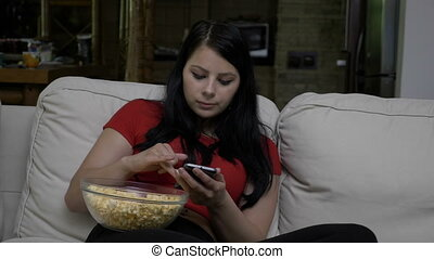 Woman sitting on the couch with a bowl of popcorn in her lap and texting on smart phone during tv commercial break