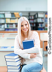 Woman sitting on the desk with pile of books