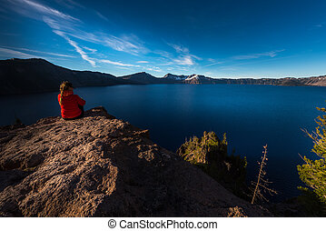Woman Sitting on the Edge of a Cliff looking at Crater Lake Oregon