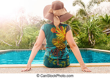 Woman sitting on the edge of a pool in tropical resort.