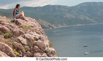 Woman sitting on the edge of  cliff