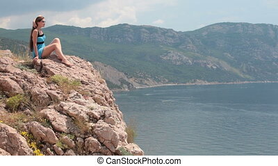 Woman sitting on the edge of cliff - Woman sitting on the...