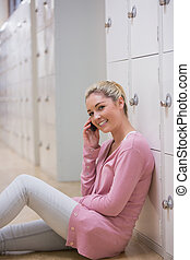 Woman sitting on the floor against lockers at the hallway while phoning and smiling