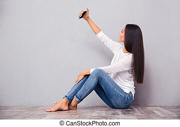 Woman sitting on the floor and making selfie photo
