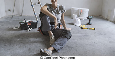 Woman sitting on the floor and planning a home renovation