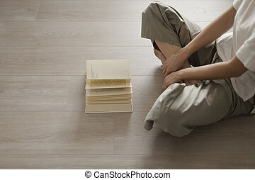 Woman sitting on the floor and reading a book