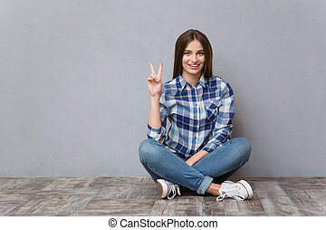 Woman sitting on the floor and showing victory sign