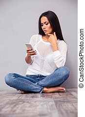 Woman sitting on the floor and using smartphon