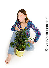 Woman sitting on the floor cutting plant
