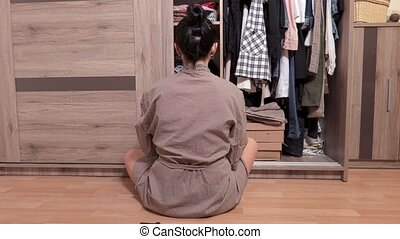 Woman sitting on the floor near wardrobe and choosing...