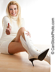 woman sitting on the floor putting on boots