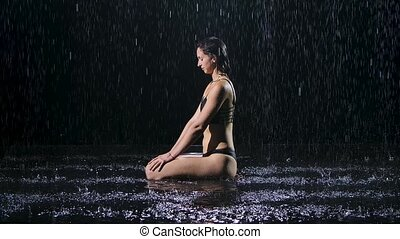 Woman sitting on the floor under rain folds her hands in a lotus pose and achievement of peace and tranquility. Doing complex of stretching yoga for woman health. Shot in a dark studio on the surface of the water. Black background. Slow motion.