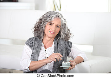 Woman sitting on the floor with a cup of coffee