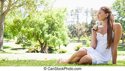 Woman sitting on the grass with a flower
