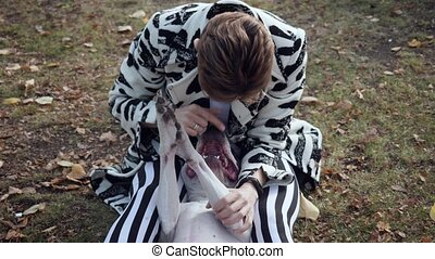 Woman sitting on the ground and embracing her stafford dog....