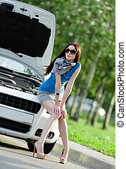 Woman sitting on the hood of the broken car