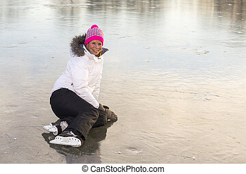 Woman sitting on the ice skating.