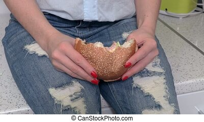 Woman sitting on the kitchen table and eating burger