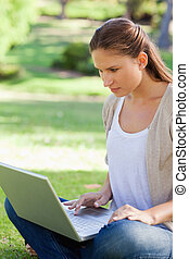 Woman sitting on the lawn with her notebook