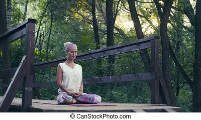 Woman sitting on the old bridge in a park