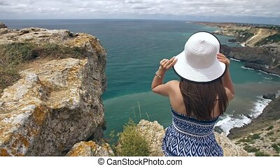 Woman sitting on the rock and watching seascape