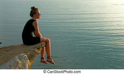 Woman sitting  on the rock