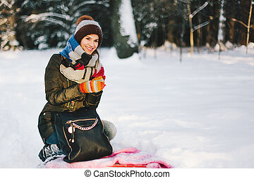 Woman sitting on the snow in forest