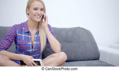 Woman sitting on the sofa, talking on the phone.