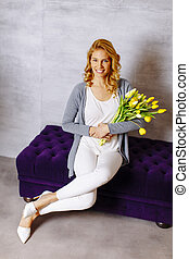 Woman sitting on the sofa with a bouquet of yellow tulips