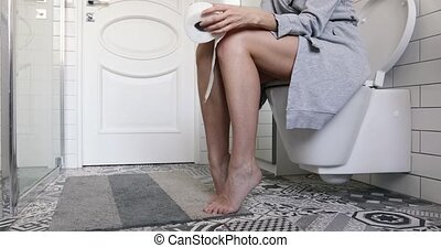 Woman sitting on the toilet holding toilet paper in her...