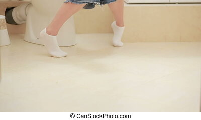 woman sitting on toilet in the bathroom. girl using her...