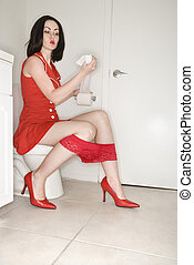Woman sitting on toilet.