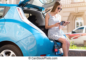 Woman sitting on trunk with tablet